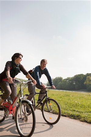 Couple riding bicycles on rural road Stock Photo - Premium Royalty-Free, Code: 649-06112674
