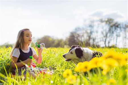 Girl blowing bubbles with dog in field Stock Photo - Premium Royalty-Free, Code: 649-06112835