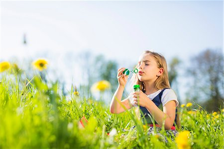Girl blowing bubbles in field Stock Photo - Premium Royalty-Free, Code: 649-06112836