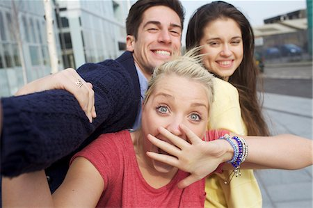 Friends smiling together on city street Stock Photo - Premium Royalty-Free, Code: 649-06113019