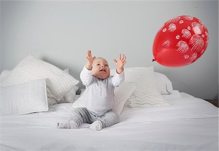 reaching - Baby boy playing with balloon on bed Stock Photo - Premium Royalty-Free, Code: 649-06113151
