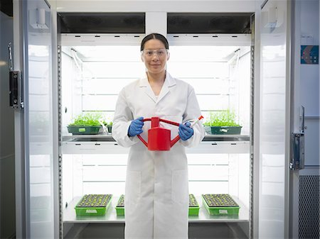 Scientist watering plants in container Stock Photo - Premium Royalty-Free, Code: 649-06113297