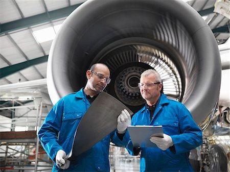 Workers talking in airplane hangar Stock Photo - Premium Royalty-Free, Code: 649-06113328