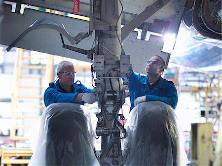 Worker adjusting airplane machinery Stock Photo - Premium Royalty-Free, Code: 649-06113345