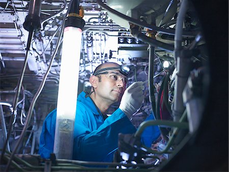 Worker adjusting airplane machinery Stock Photo - Premium Royalty-Free, Code: 649-06113343