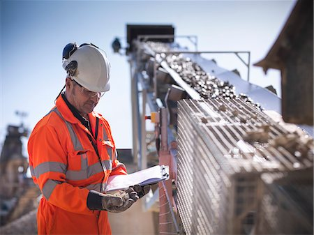 Worker with clipboard by conveyor belt Stock Photo - Premium Royalty-Free, Code: 649-06113377