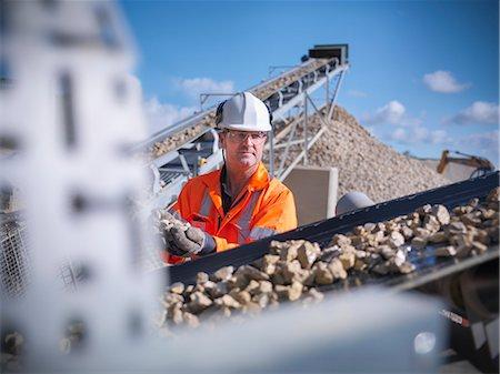 Worker examining stones on conveyor belt Stock Photo - Premium Royalty-Free, Code: 649-06113378