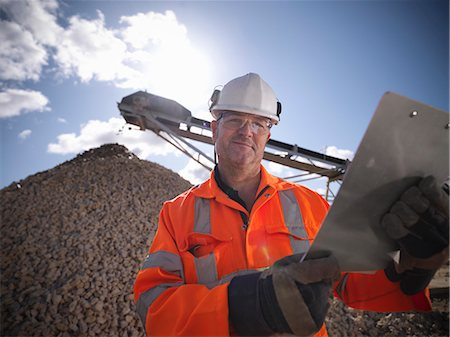 Worker standing by pile of stones Stock Photo - Premium Royalty-Free, Code: 649-06113381
