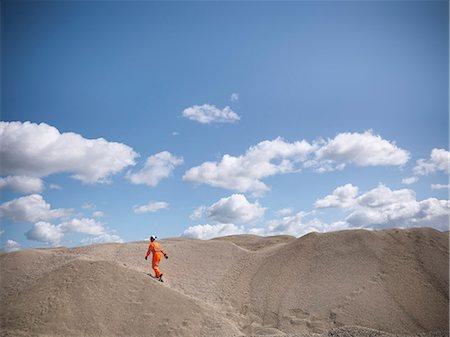 Worker climbing sand dunes in quarry Stock Photo - Premium Royalty-Free, Code: 649-06113393