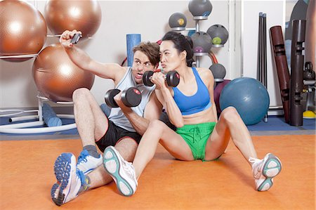 funny pose - Couple lifting weights in gym Stock Photo - Premium Royalty-Free, Code: 649-06113484
