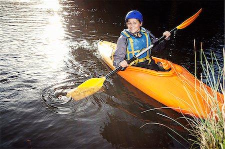 Kayaker rowing in still lake Stock Photo - Premium Royalty-Free, Code: 649-06113549