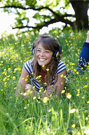 scenic and spring (season) - Woman listening to headphones in grass Stock Photo - Premium Royalty-Free, Code: 649-06113567