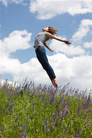 scenic and spring (season) - Woman jumping over tall grass Stock Photo - Premium Royalty-Free, Code: 649-06113575