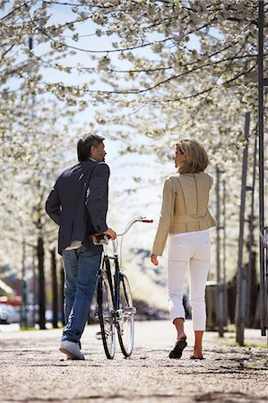 Couple walking bicycle in park Stock Photo - Premium Royalty-Free, Code: 649-06113630