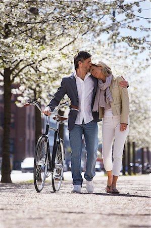 Couple walking bicycle in park Stock Photo - Premium Royalty-Free, Code: 649-06113631