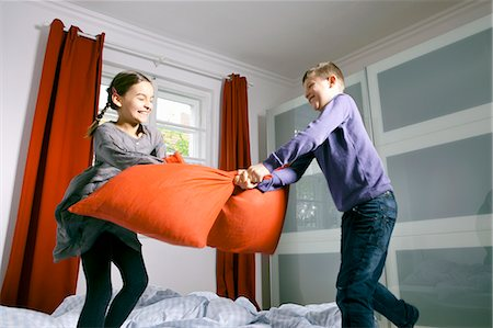 Children having pillow fight on bed Stock Photo - Premium Royalty-Free, Code: 649-06113827