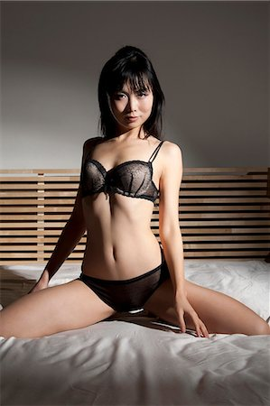 desire - Woman in lingerie sitting on bed Stock Photo - Premium Royalty-Free, Code: 649-06164331