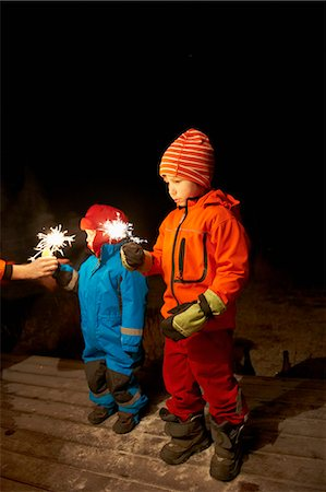 Boys playing with sparkler outdoors Stock Photo - Premium Royalty-Free, Code: 649-06164684