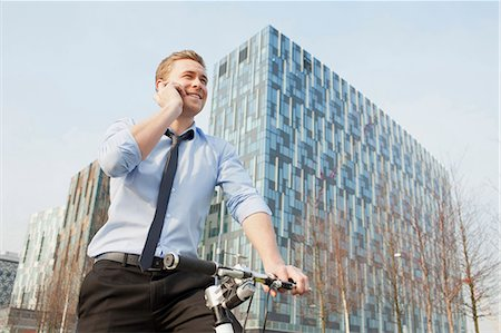 Businessman riding bicycle outdoors Stock Photo - Premium Royalty-Free, Code: 649-06164735