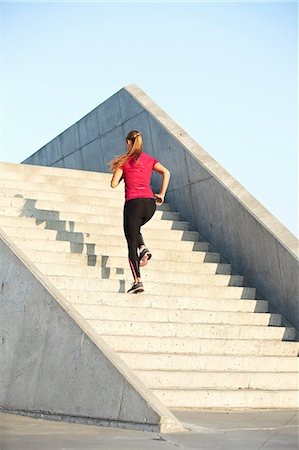 Woman running on staircase Stock Photo - Premium Royalty-Free, Code: 649-06164819