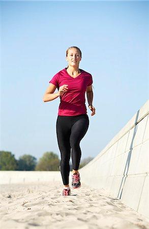 Woman running in sand Stock Photo - Premium Royalty-Free, Code: 649-06164825