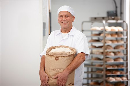 Chef carrying sack of flour in kitchen Stock Photo - Premium Royalty-Free, Code: 649-06165020