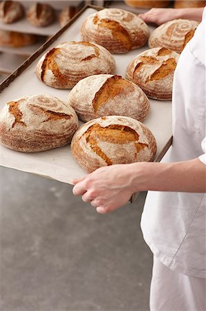 Chef carrying tray of bread in kitchen Stock Photo - Premium Royalty-Free, Code: 649-06165036