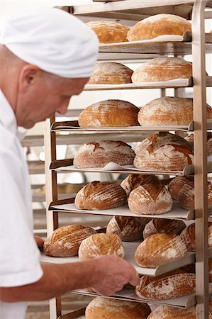 Chef putting tray of bread on rack Stock Photo - Premium Royalty-Free, Code: 649-06165048
