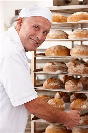 Chef putting tray of bread on rack Stock Photo - Premium Royalty-Free, Code: 649-06165049