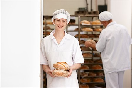 Chef holding loaves of bread in kitchen Stock Photo - Premium Royalty-Free, Code: 649-06165042
