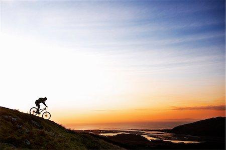 Mountain biker riding down hillside Stock Photo - Premium Royalty-Free, Code: 649-06165075
