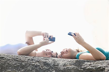 Teenage girls using cell phones outdoors Stock Photo - Premium Royalty-Free, Code: 649-06165174