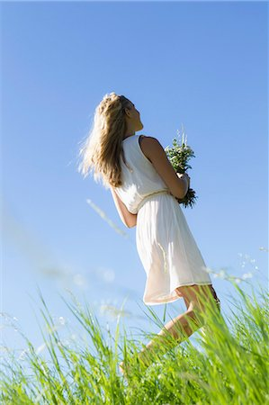 Woman carrying bouquet in tall grass Stock Photo - Premium Royalty-Free, Code: 649-06304840