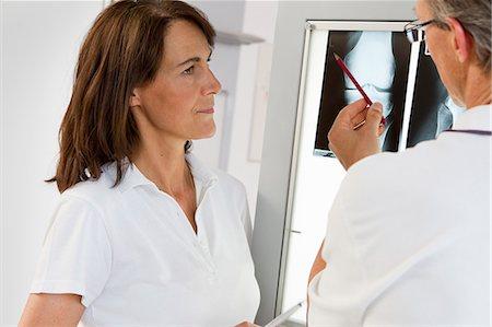 surgeons hands - Doctor and nurse examining x-rays Stock Photo - Premium Royalty-