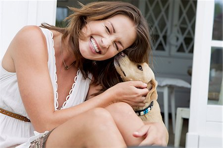 dog and woman and love - Smiling woman playing with dog Stock Photo - Premium Royalty-Free, Code: 649-06304961