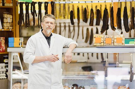 Butcher standing at meat counter Stock Photo - Premium Royalty-Free, Code: 649-06305048