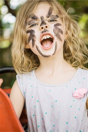 funny pose - Girl wearing face paint outdoors Stock Photo - Premium Royalty-Free, Code: 649-06305087