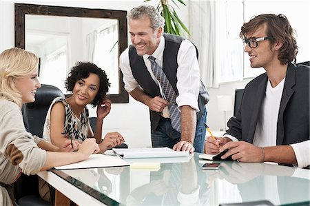 partnership - Business people working together at desk Stock Photo - Premium Royalty-Free, Code: 649-06305274