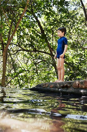Boy standing by river in forest Stock Photo - Premium Royalty-Free, Code: 649-06305348