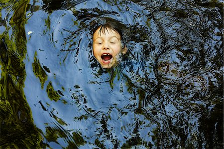 Laughing boy swimming in river Stock Photo - Premium Royalty-Free, Code: 649-06305350