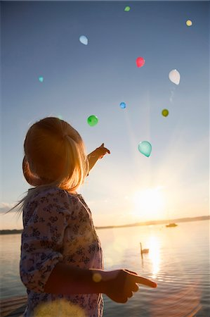 Girl watching balloons floating away Stock Photo - Premium Royalty-Free, Code: 649-06305408