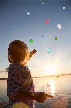 Girl watching balloons floating away Stock Photo - Premium Royalty-Free, Code: 649-06305408