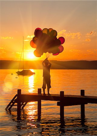 release - Boy holding balloons on wooden dock Stock Photo - Premium Royalty-Free, Code: 649-06305409
