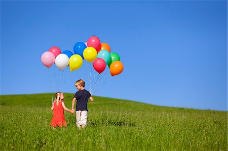 Children with colorful balloons in grass Stock Photo - Premium Royalty-Free, Code: 649-06305401