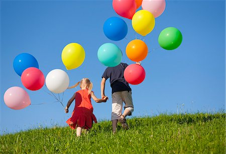 Children with colorful balloons in grass Stock Photo - Premium Royalty-Free, Code: 649-06305403