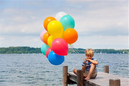 Boy holding balloons on wooden pier Stock Photo - Premium Royalty-Free, Code: 649-06305418