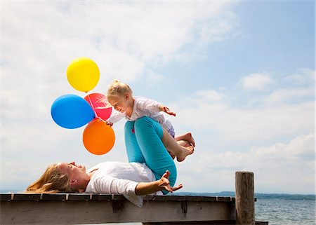flying happy woman images - Mother and daughter playing on pier Stock Photo - Premium Royalty-Free, Code: 649-06305426