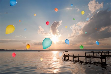 Balloons floating over still lake Stock Photo - Premium Royalty-Free, Code: 649-06305429