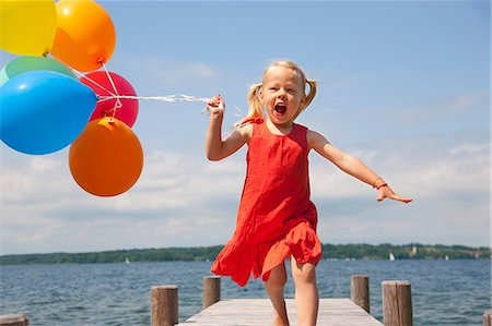 Girl holding balloons on wooden pier Stock Photo - Premium Royalty-Free, Code: 649-06305421