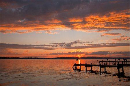 Sun setting over still rural lake Stock Photo - Premium Royalty-Free, Code: 649-06305430